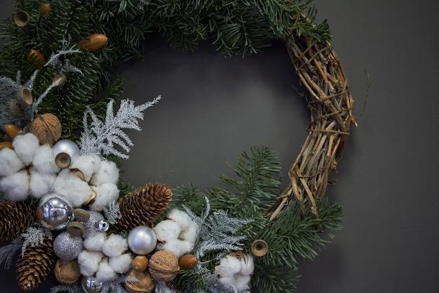 Weihnachtskranz aus weinreben mit tannenzweigen, weihnachtskugeln und naturmaterialien,