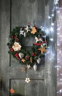 Weihnachtskranz, der in der rustikalen tür hängt