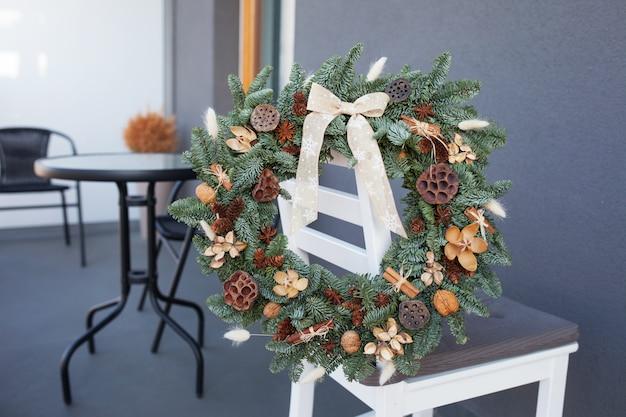 Weihnachtskranz gemacht von den natürlichen tannenzweigen, die an der rückseite des weißen stuhls hängen