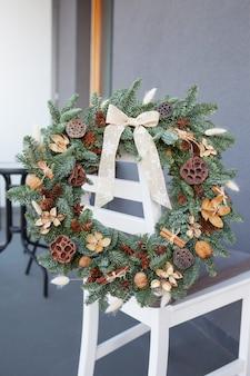 Weihnachtskranz gemacht von den natürlichen tannenzweigen, die an der rückseite des weißen stuhls hängen.
