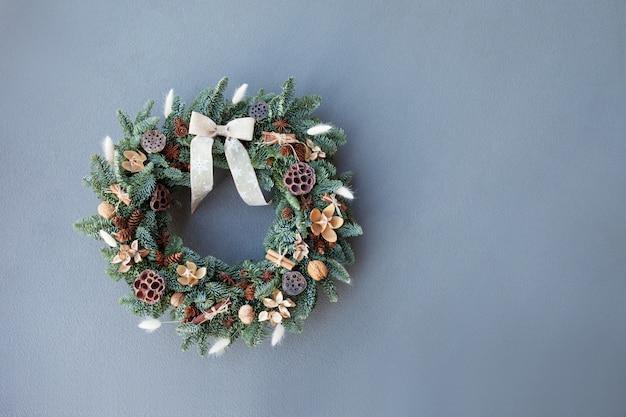 Weihnachtskranz gemacht von den natürlichen tannenzweigen, die an einer grauen wand hängen