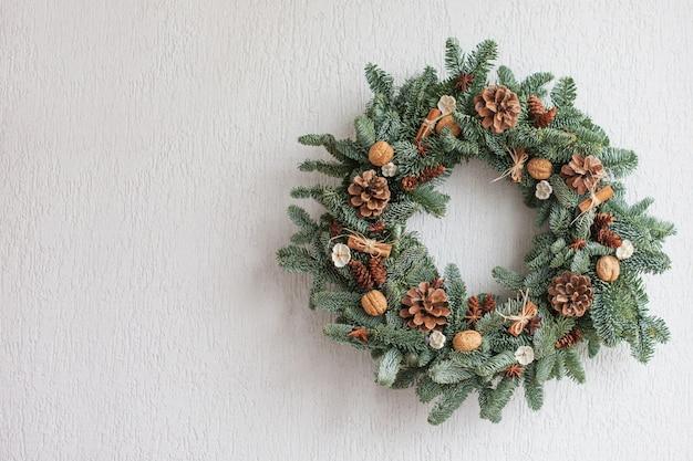 Weihnachtskranz gemacht von den natürlichen tannenzweigen, die an einer weißen wand hängen. kranz mit natürlichen ornamenten: beulen, walnüsse, zimt, zapfen. neujahr und weihnachten dekor. kopieren sie platz