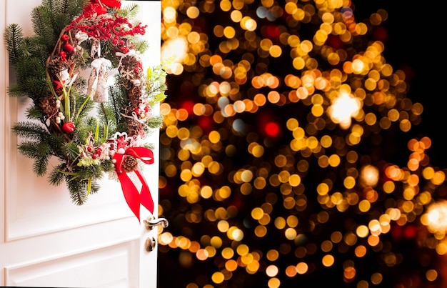 Weihnachtskranz hängt an den weißen türen. rote und weiße elemente, schleife zum dekorieren des ferienhauses