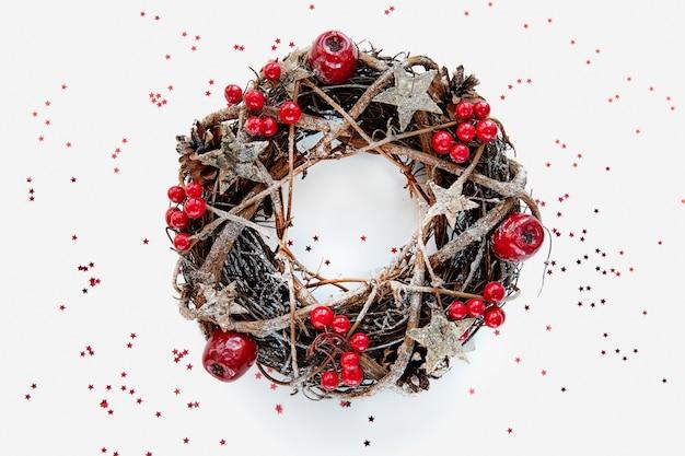 Weihnachtskranz hergestellt aus zweigen, die mit goldenen holzsternen und roten beerenblasen auf weißem hintergrund verziert sind. kreatives diy-bastelhobby.
