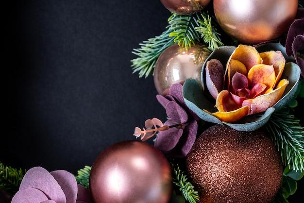 Weihnachtskranz mit blumendekoration auf schwarzem. flach liegen