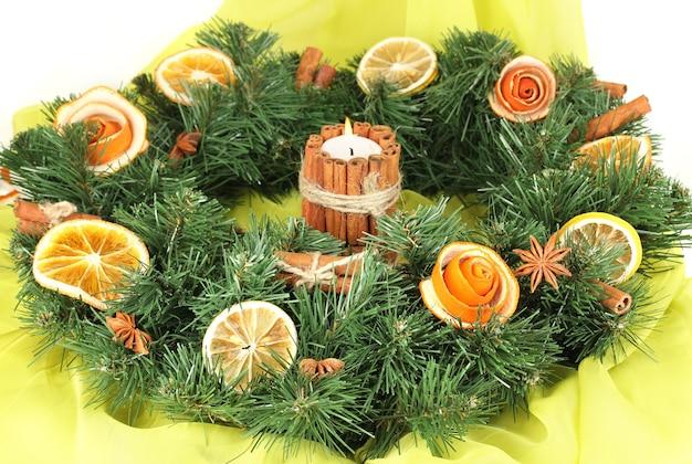 Weihnachtskranz mit brennender kerze auf stoffhintergrund