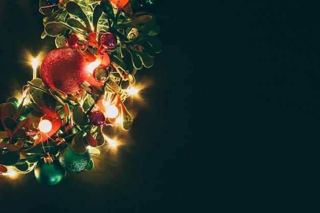 Weihnachtskranz mit dekorativem licht auf dunklem hölzernem hintergrund