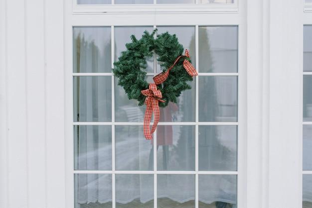 Weihnachtskranz mit einer roten schleife auf weißem fenster in einem privathaus
