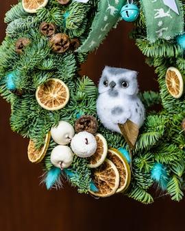 Weihnachtskranz mit früchten und einer eule