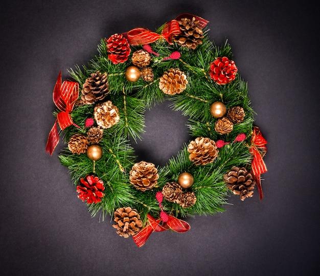 Weihnachtskranz mit pinecones auf schwarzem