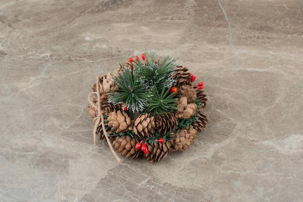 Weihnachtskranz mit roten perlen und zapfen auf marmor.
