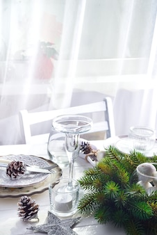Weihnachtskranz mit spielwaren auf dem tisch mit silver christmas table setting