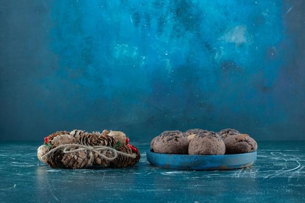 Weihnachtskranz und eine portion kekse auf blau.