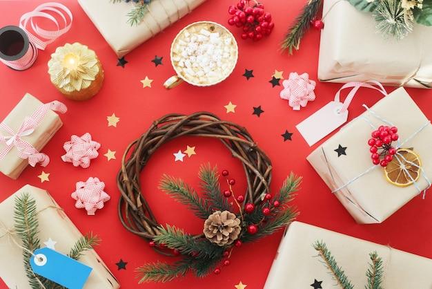 Weihnachtskranz und geschenke unter dekorationen neben einer tasse kakao