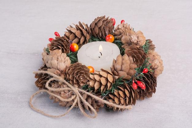 Weihnachtskranz und kerze auf weißer oberfläche