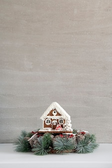 Weihnachtskranz und lebkuchenhaus auf grauem hintergrund. neujahr und weihnachten. speicherplatz kopieren.