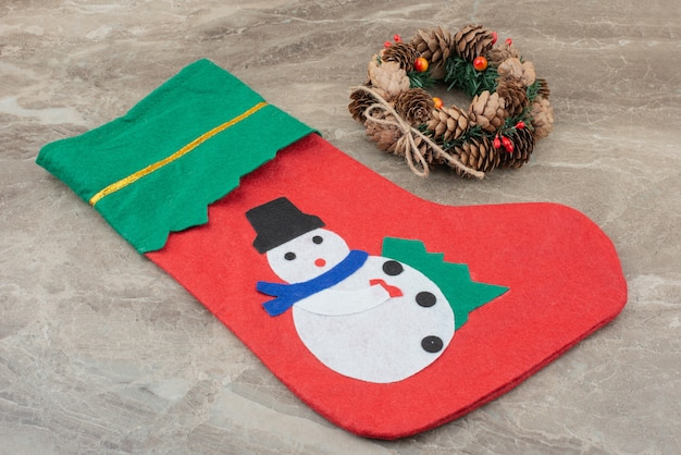 Weihnachtskranz und socke auf marmor.