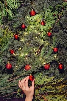 Weihnachtskranz, weibliche hände nahaufnahme macht einen kranz aus fichte und verziert mit roten kugeln,