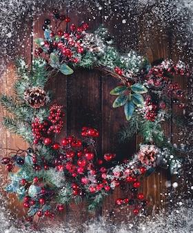 Weihnachtskranzdekoration mit tannenzapfen und weißdornbeeren auf holzoberfläche