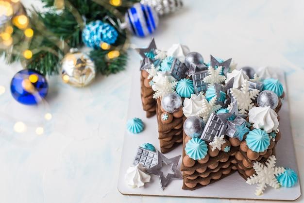 Weihnachtskuchen in form eines weihnachtsbaumes. weihnachtskuchen mit schokoladenkugeln und schneeflocken. schokolade mit blauer dekoration.
