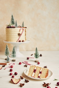 Weihnachtskuchen mit dekorationen und einem stück kuchen auf einem teller