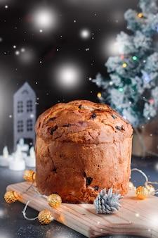 Weihnachtskuchen mit rosinen und kandierten früchten mit weihnachtsdekor und kerzen, stillleben