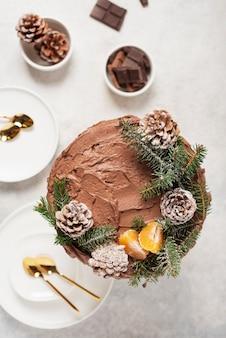 Weihnachtskuchen mit schokolade verziert mit tannenzapfen und kiefer auf hellem hintergrund