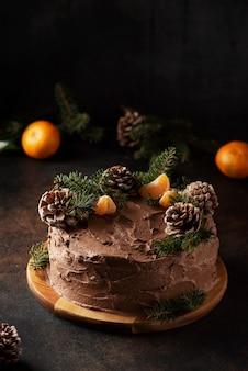Weihnachtskuchen mit schokolade verziert mit tannenzapfen und kiefer, selektives fokusbild