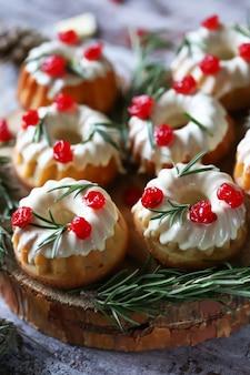 Weihnachtskuchen mit weißem zuckerguss, roten beeren und rosmarin. weihnachtsdekoration. selektiver fokus.