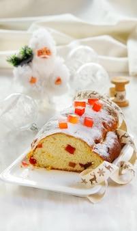 Weihnachtskuchen, verziert mit zuckerpulver, obstkuchen auf dem weißen steinhintergrund