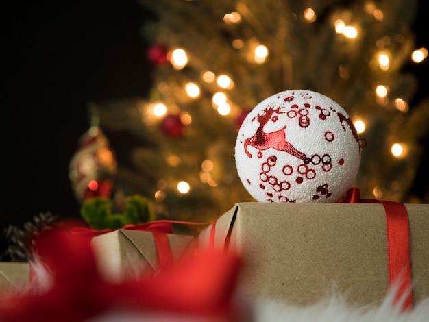 Weihnachtskugel auf geschenkbox gegen weihnachtsbaumbeleuchtung zu hause