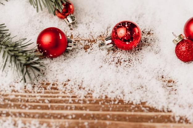 Weihnachtskugel auf schneebedecktem holztisch,