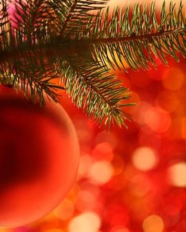 Weihnachtskugel auf tannenbaum vor rotem unscharfen hintergrund