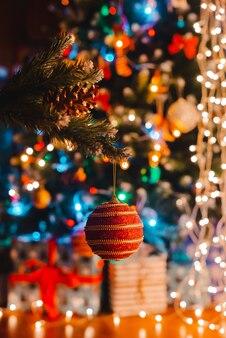 Weihnachtskugel hängt an einem geschmückten tannenbaum