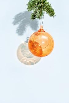 Weihnachtskugel hängt an tannenzweig an blauer wand orangefarbenes glas transparent