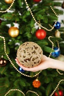 Weihnachtskugel in der hand auf weihnachtsbaumhintergrund