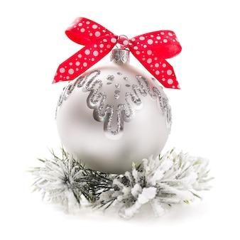 Weihnachtskugel mit rotem band auf weißem hintergrund