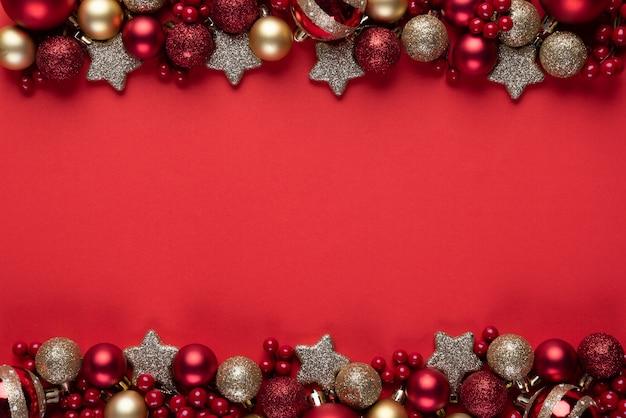 Weihnachtskugel und rote beeren auf rotem hintergrund