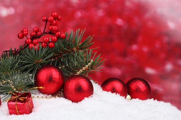 Weihnachtskugel und spielzeug mit grünem baum im schnee auf rot