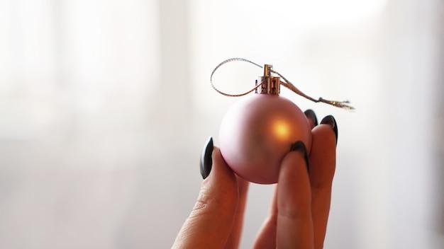 Weihnachtskugel zur hand mit weißem hintergrund unscharf