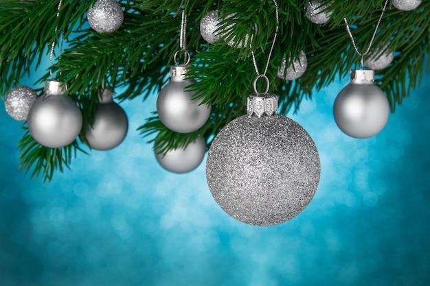 Weihnachtskugeln auf einem weihnachtsbaumzweig auf blauem unscharfem glänzendem hintergrund