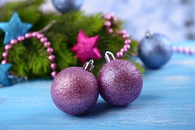 Weihnachtskugeln auf tannenbaum auf blauem holztisch Premium Fotos