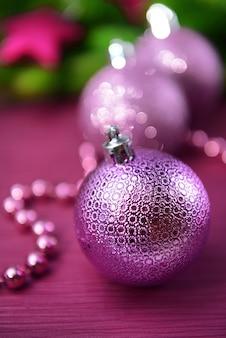 Weihnachtskugeln auf tannenbaum auf lila tisch
