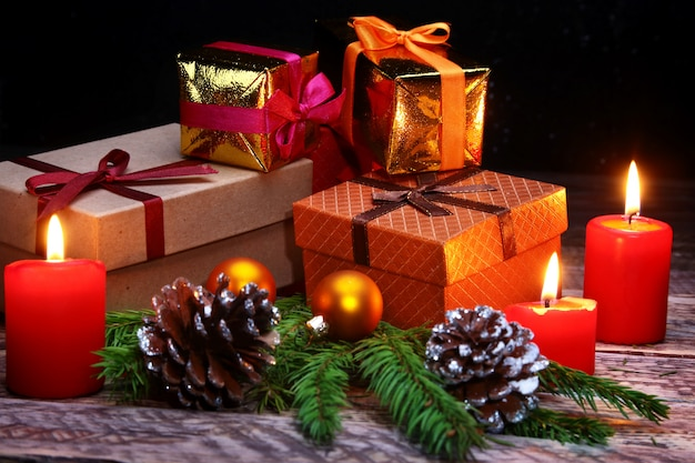 Weihnachtskugeln, geschenkboxen und kerzen.