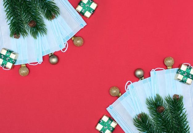Weihnachtskugeln, geschenke, medizinische schutzgesichtsmasken, fichte mit tannenzapfen auf rotem hintergrund.