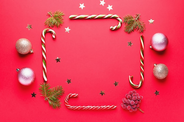 Weihnachtskugeln, goldene dekorationen, zuckerstangenrahmen, konfetti auf rotem hintergrund mit kopienraum. weihnachtskarte mit ornamenten, ansicht von oben