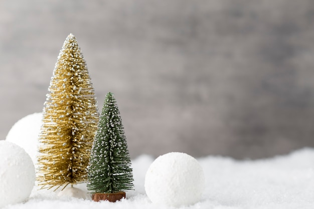 Weihnachtskugeln, grußkarte und tannenbaum auf schnee