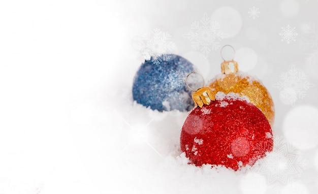 Weihnachtskugeln im schnee eingebettet