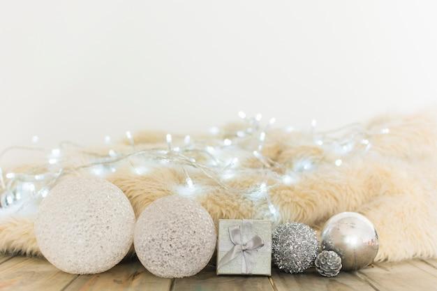 Weihnachtskugeln in der nähe von lichterketten und bettdecke