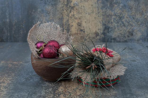 Weihnachtskugeln in der schüssel auf marmorhintergrund. hochwertiges foto